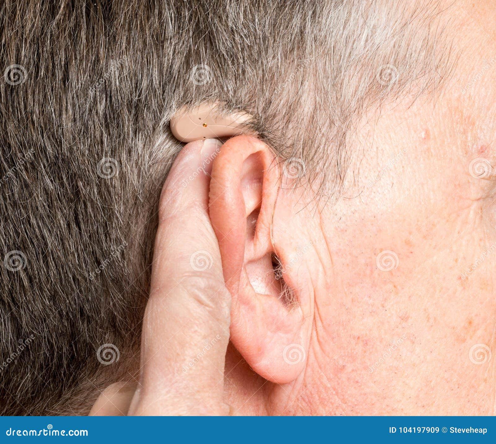 Sluit omhoog van een uiterst klein modern gehoorapparaat achter oor