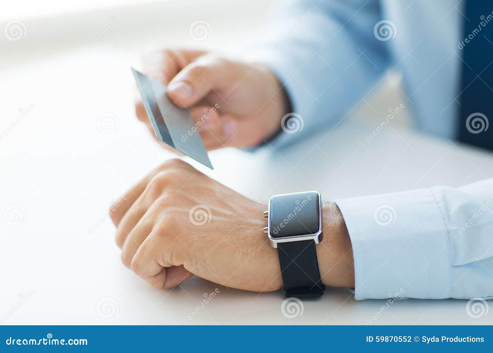 Sluit omhoog van handen met slimme horloge en creditcard