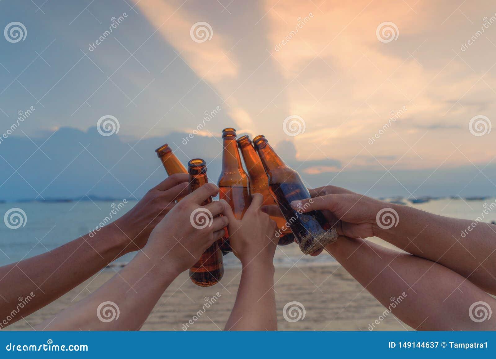 Sluit omhoog van handen van vrienden die flessen bier klinken samen en op vakantie in partij bij het strand vieren of overzees in