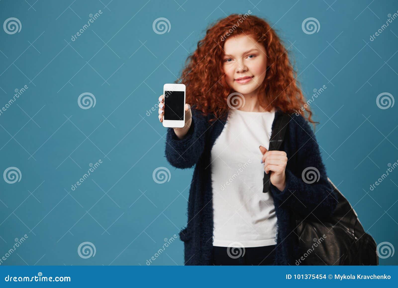 Sluit omhoog van het jonge meisje van de gemberstudent met golvend haar en sproeten die witte t-shirt en het zwarte cardigan tone