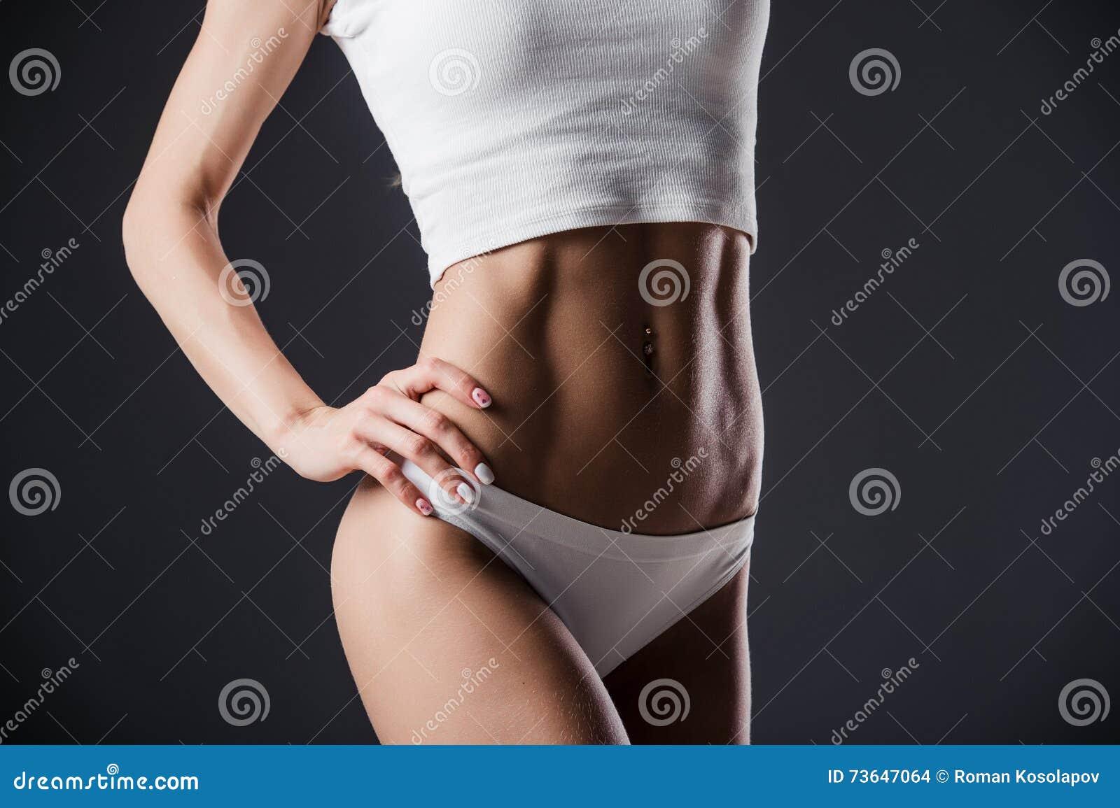 Sluit omhoog van het torso van de geschikte vrouw met haar handen op heupen Wijfje met perfecte buikspieren op zwarte achtergrond