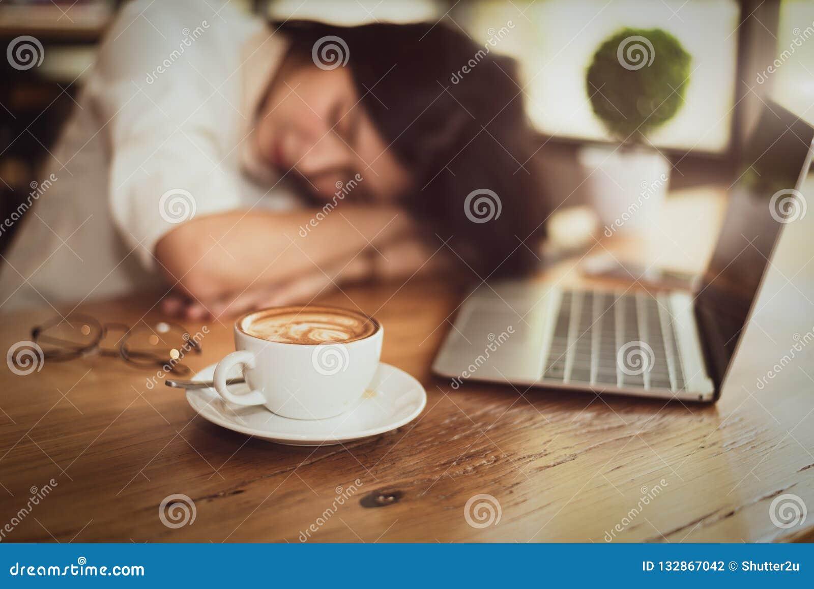 Sluit omhoog van hoogtepunt van koffie in koffiekop met bedrijfsvrouw die van het werken en laptop computerachtergrond wordt verm