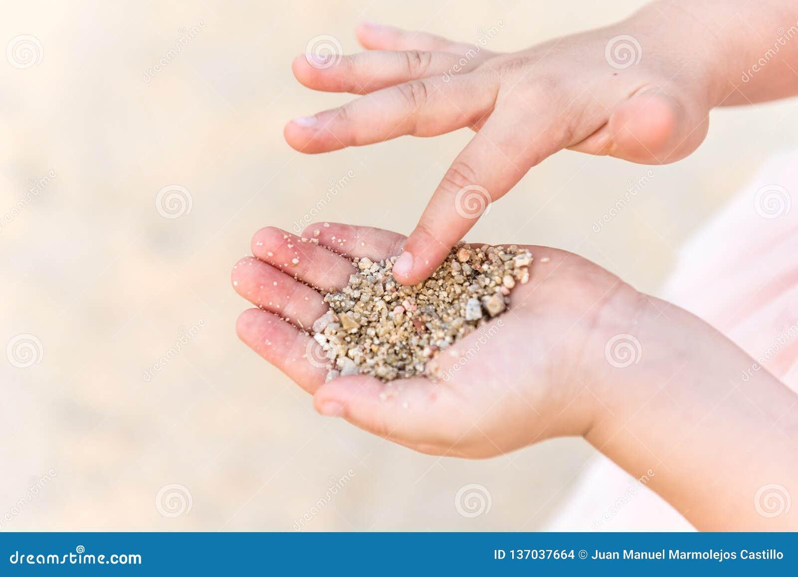Sluit omhoog van jong geitjehans het spelen met zand