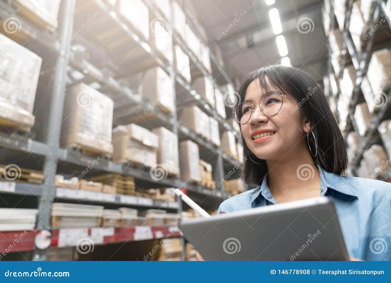 Sluit omhoog van jonge aantrekkelijke Aziatische vrouw, auditor of stagiair de inventarisatieinventaris van het personeelswerk in
