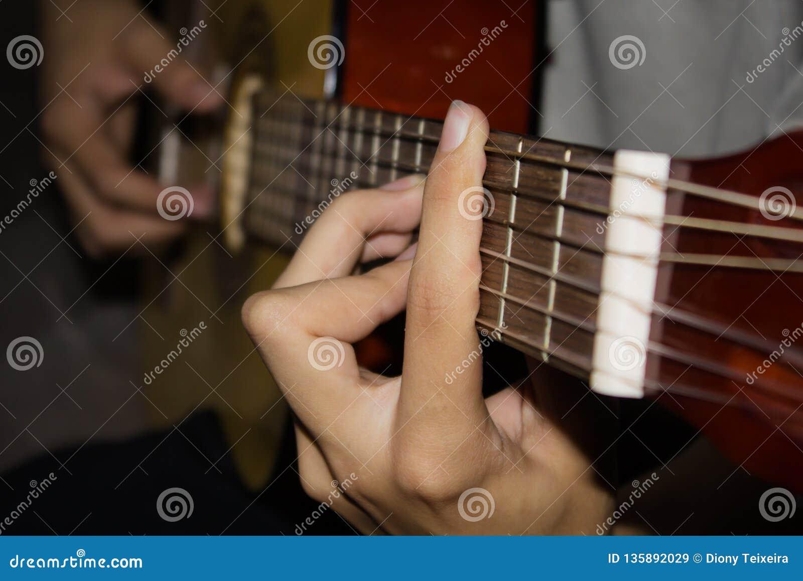 Sluit omhoog van jonge mens het spelen gitaar