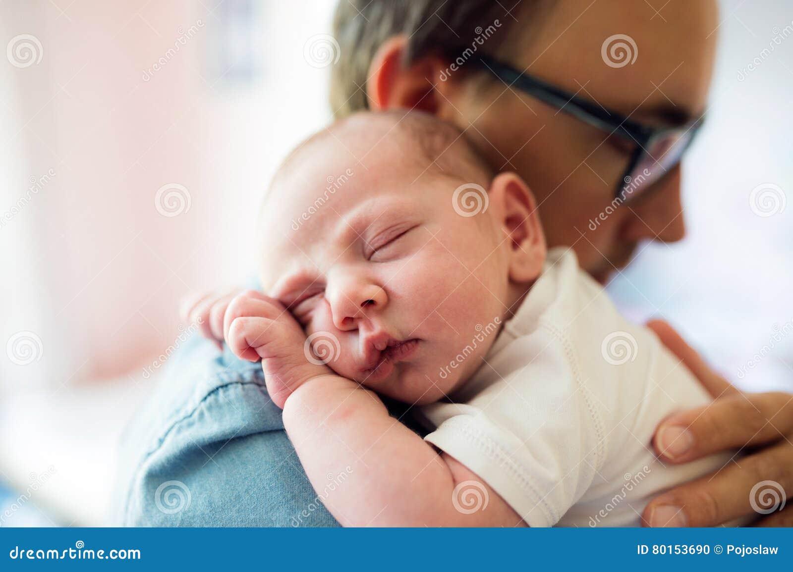 Sluit omhoog van jonge vader die zijn pasgeboren babyzoon houden