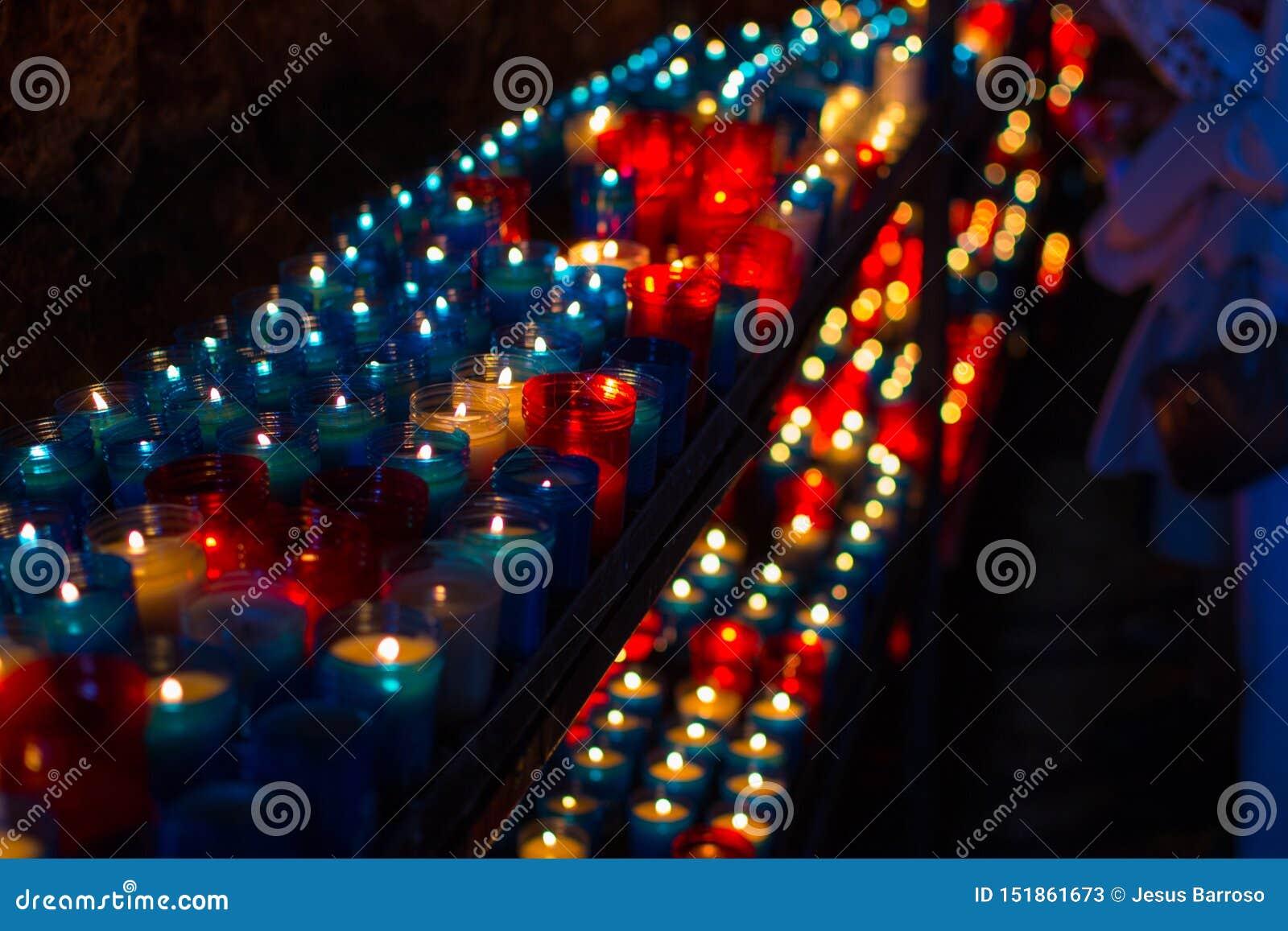 Sluit omhoog van kleurrijke kaarsen in een donkere geestelijke scène Herdenking, begrafenis, herdenkings Godsdienstige Symboliek