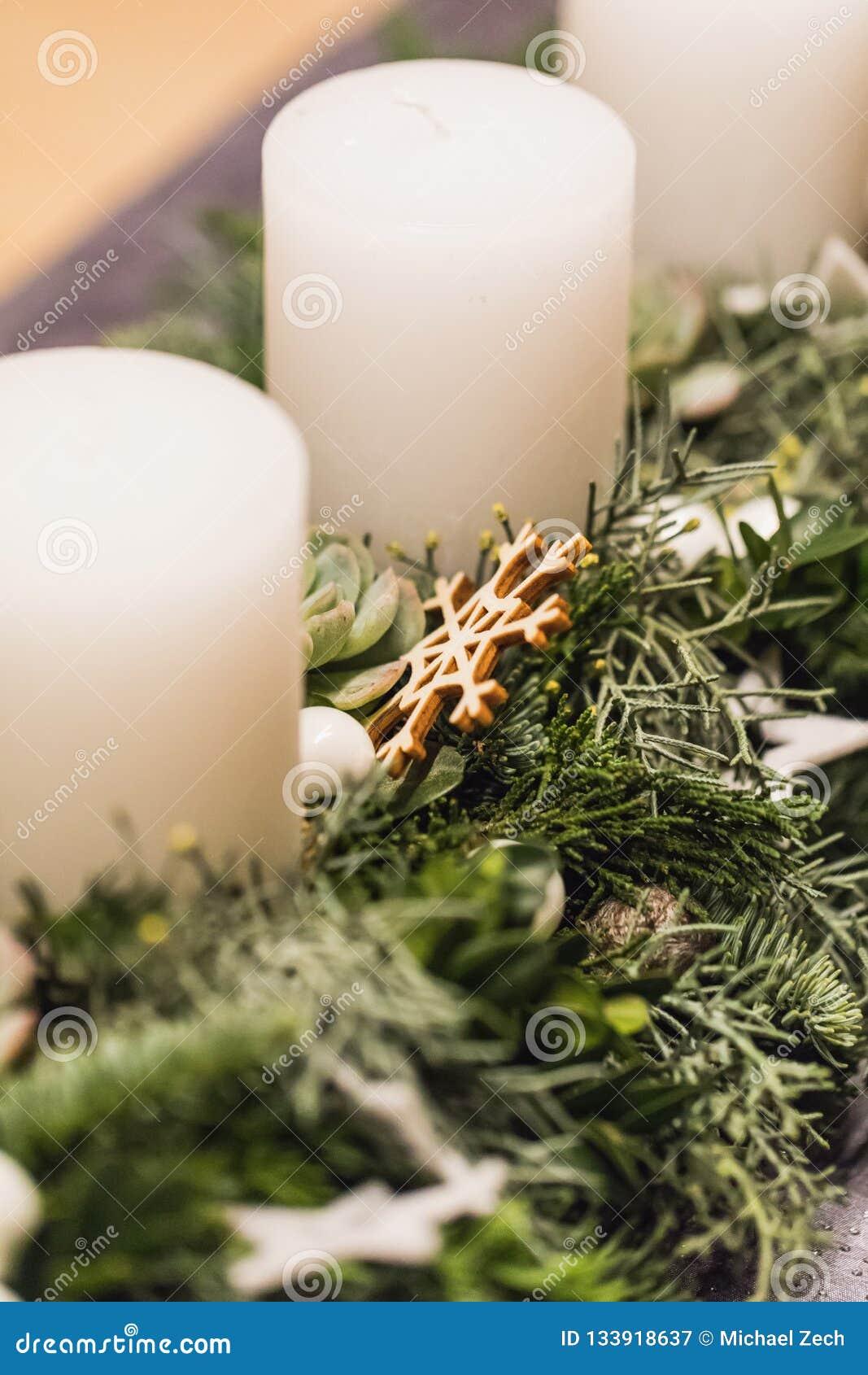 Sluit omhoog van komstkroon met witte kaarsen op Kerstmis