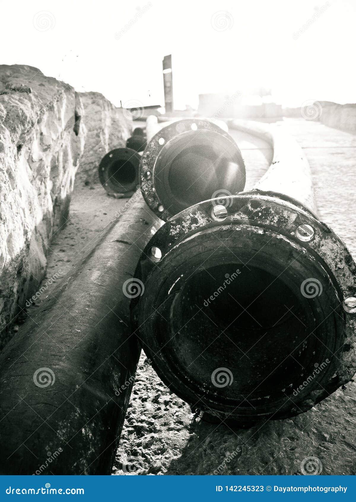 Sluit omhoog van lange pijpen ter plaatse liggend dichtbij een muur in de haven van Tel Aviv, in zwart-wit