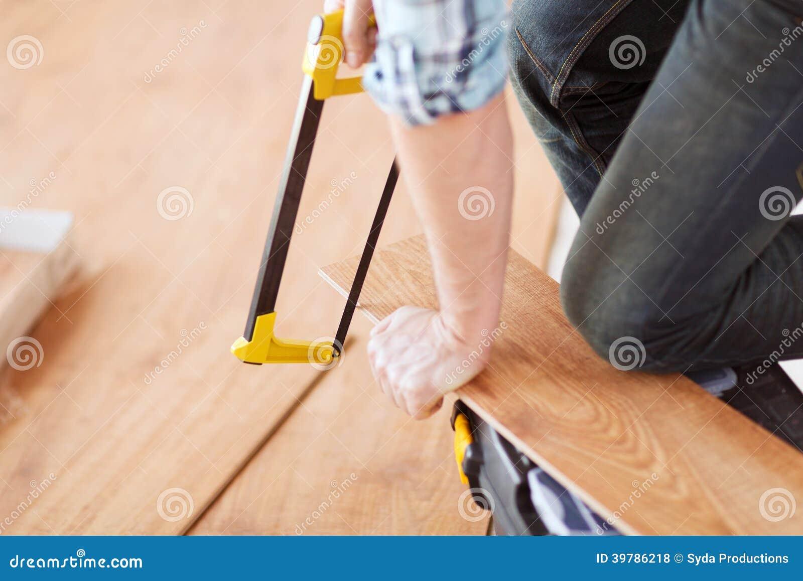 Sluit omhoog van mannelijke handen snijdend de raad van de parketvloer