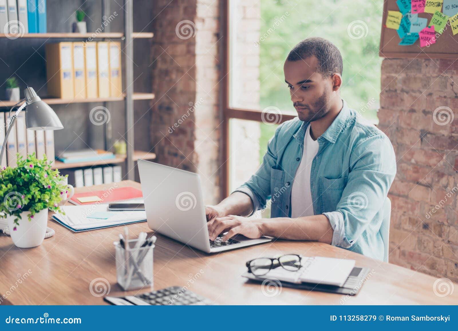 Sluit omhoog van nadenken jonge Afrikaanse knappe mens Hij draagt toevallige slim, zittend op het werk, kijkend in het laptop sch