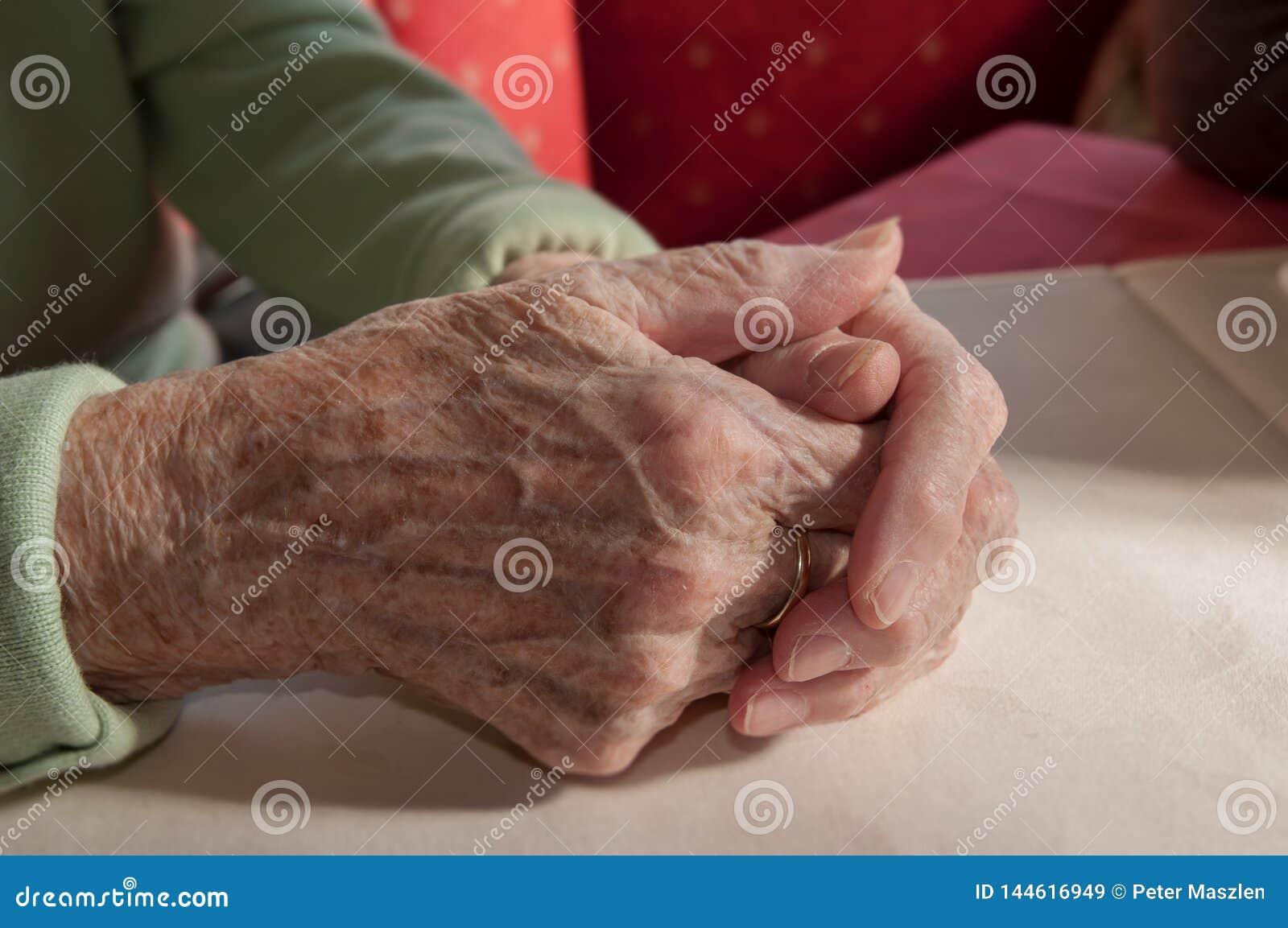 Sluit omhoog van oude gevouwen handen van hogere vrouw