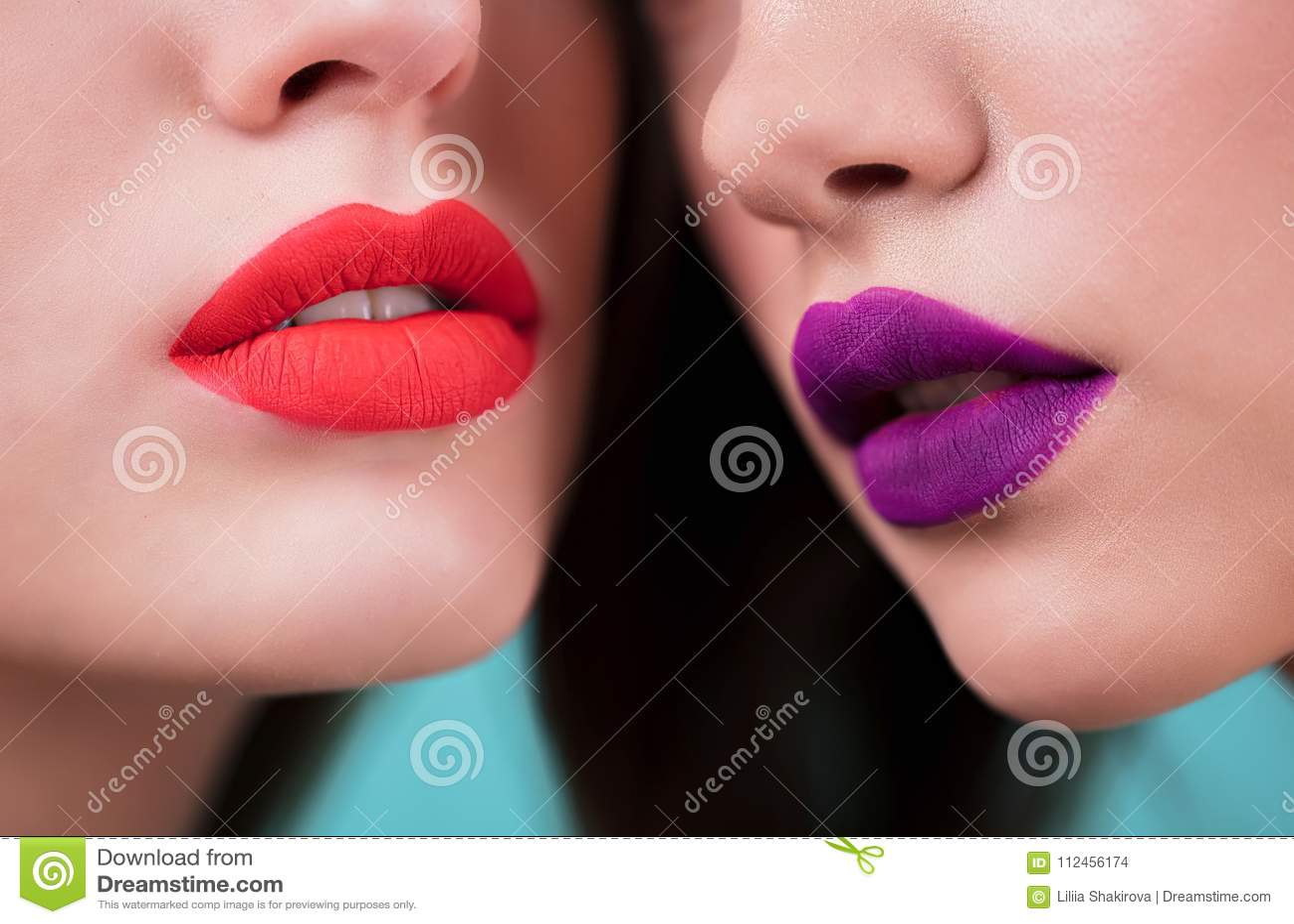 Sluit omhoog van rode en purpere lippen van twee vrouwen Schoonheidsmiddelen, make-up, lippenstift, lipgloss, gezichtszorg