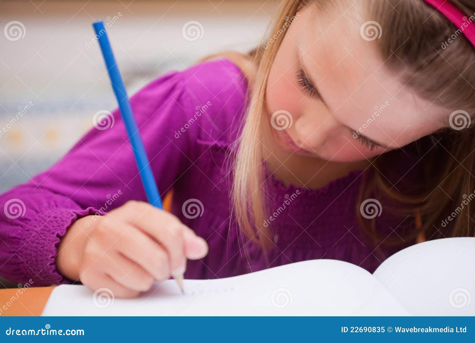 Sluit omhoog van schoolmeisje het schrijven