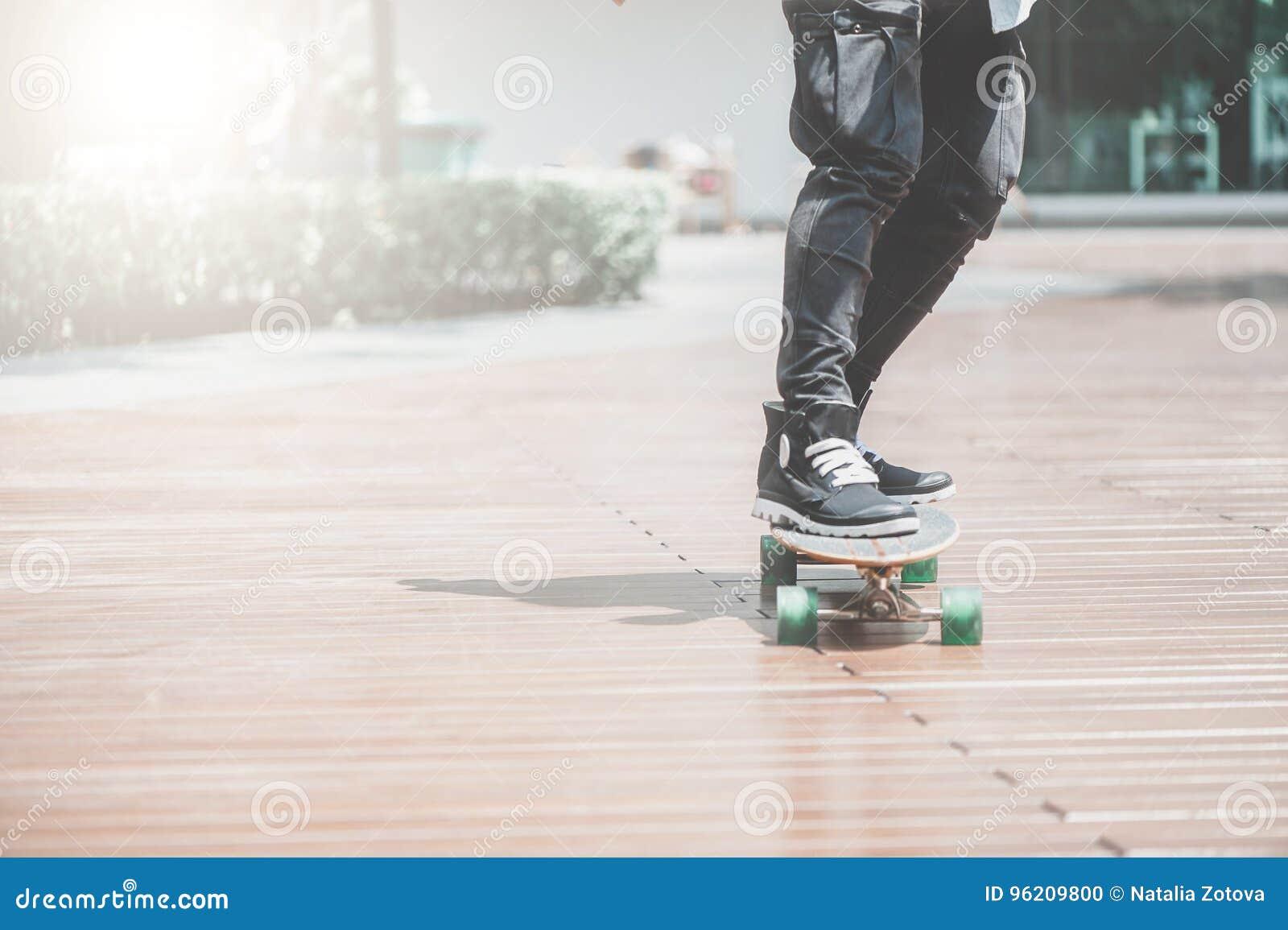 Sluit omhoog van skater& x27; s benen op longboard die bij de straat in openlucht berijden in