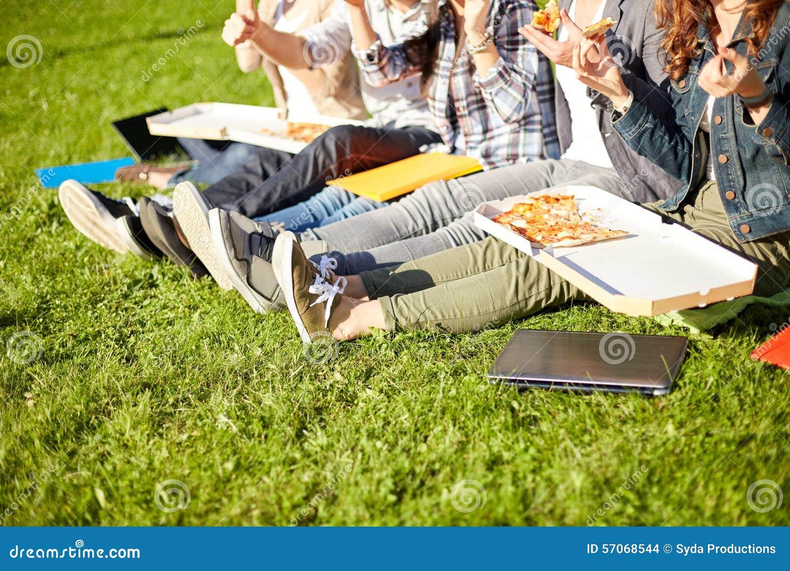 Sluit omhoog van tienerstudenten die pizza op gras eten