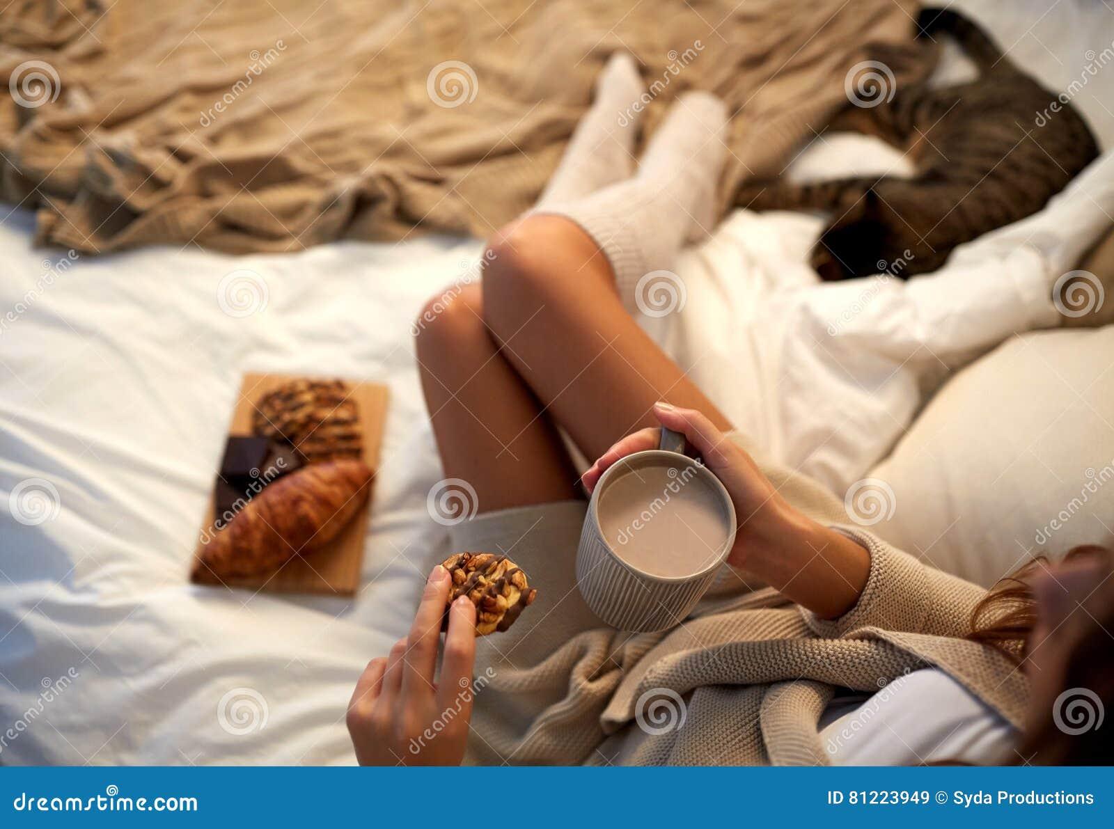 Sluit omhoog van vrouw met cacaokop en koekje in bed