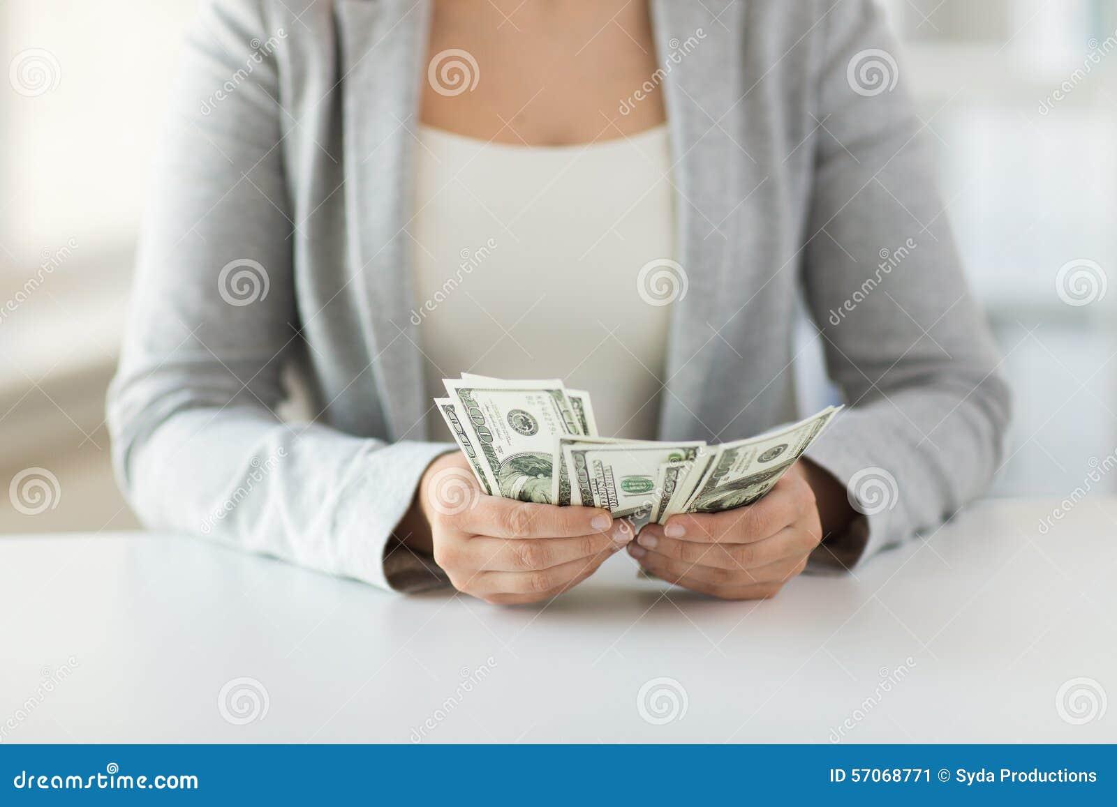 Sluit omhoog van vrouwenhanden die ons tellen dollargeld