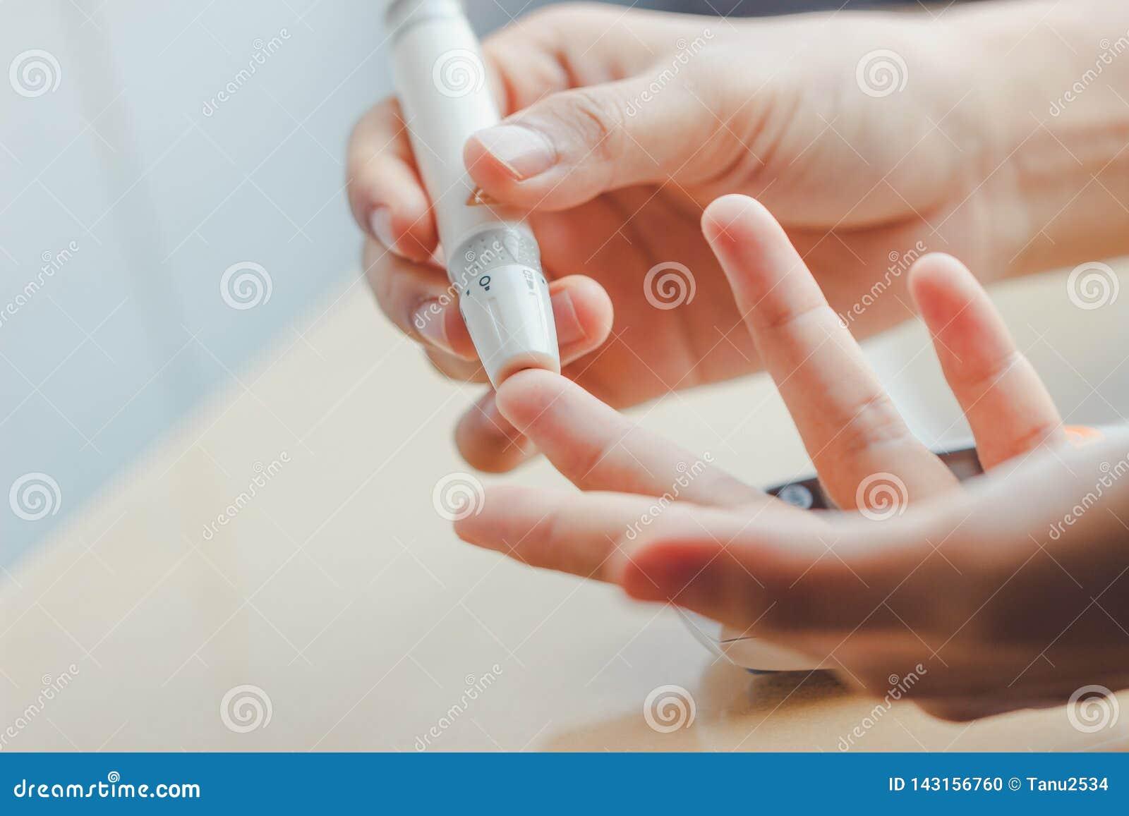 Sluit omhoog van vrouwenhanden gebruikend lancet op vinger om het niveau van de bloedsuiker door Glucosemeter te controleren gebr