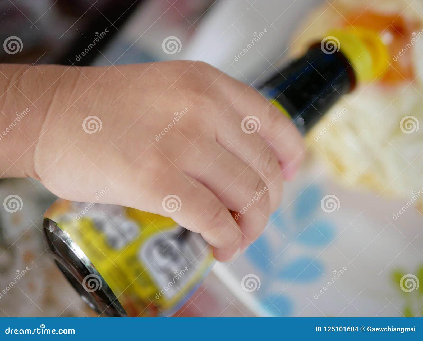 Sluit omhoog van weinig baby` s hand houdend een fles de saus van de sojaboon