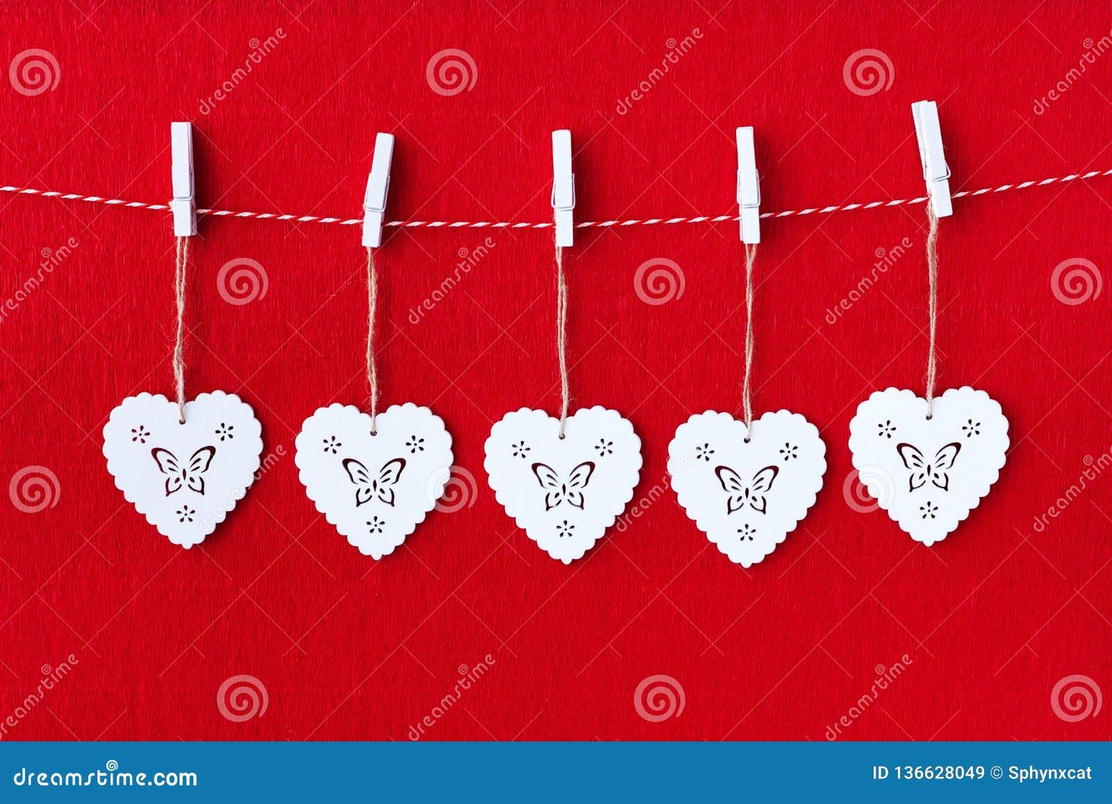Sluit omhoog van Wit houten hart simbols op rode document achtergrond