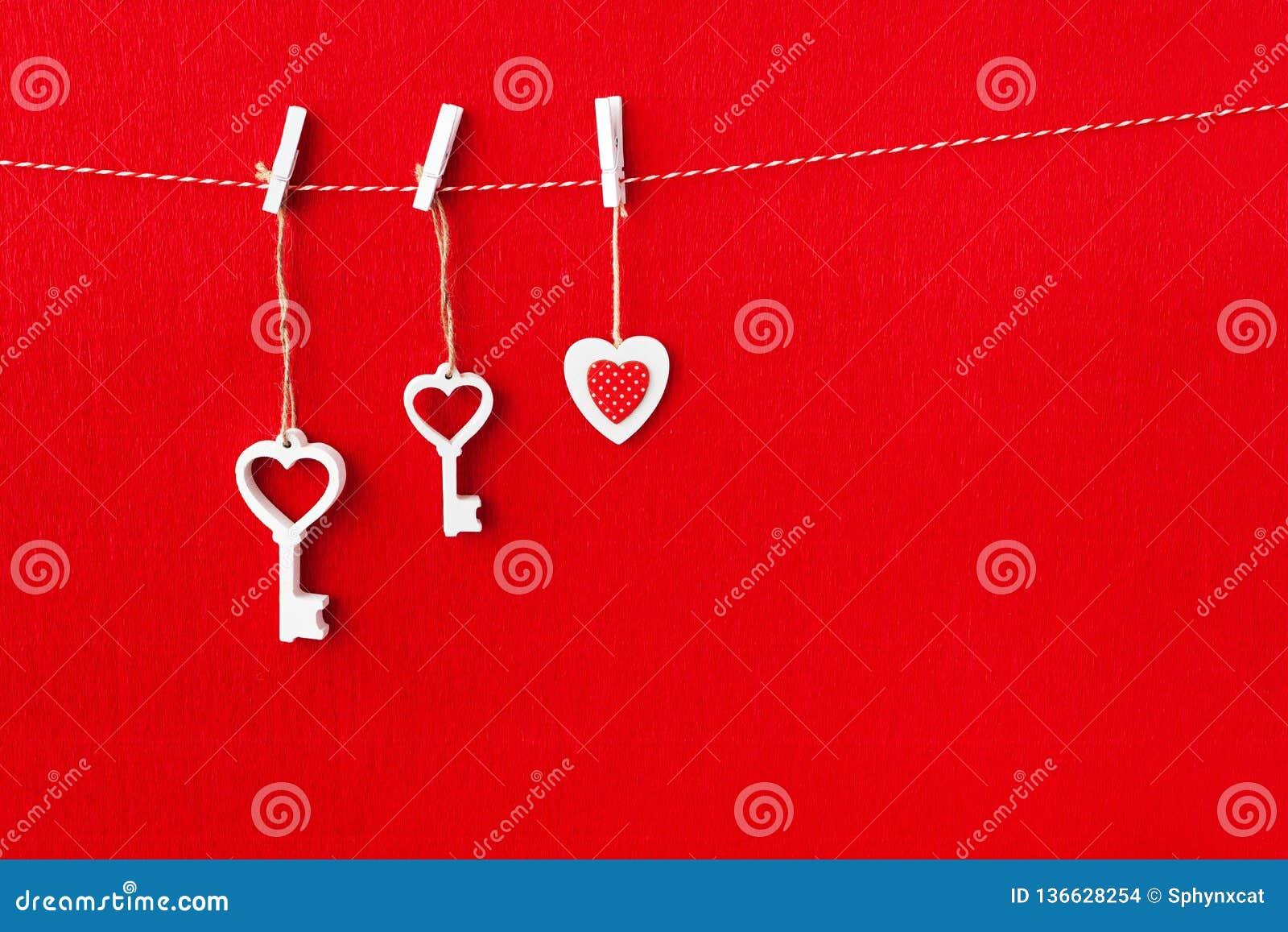 Sluit omhoog van Witte houten hartsimbol en sleutel op rode document achtergrond