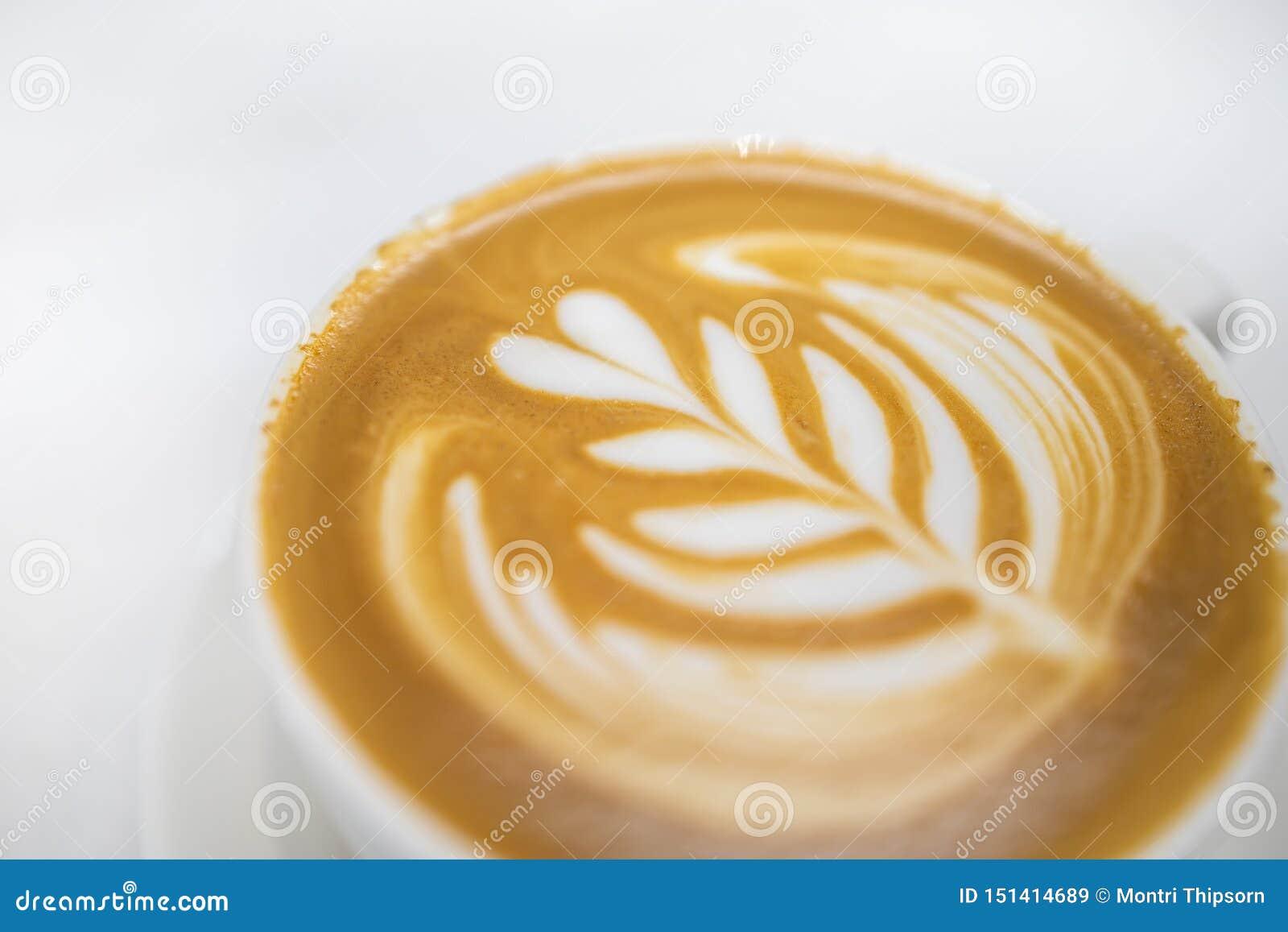 Sluit omhoog van witte kop van hete koffie latte met het hart van het melkschuim en de kunst van de bloemvorm op witte lijst