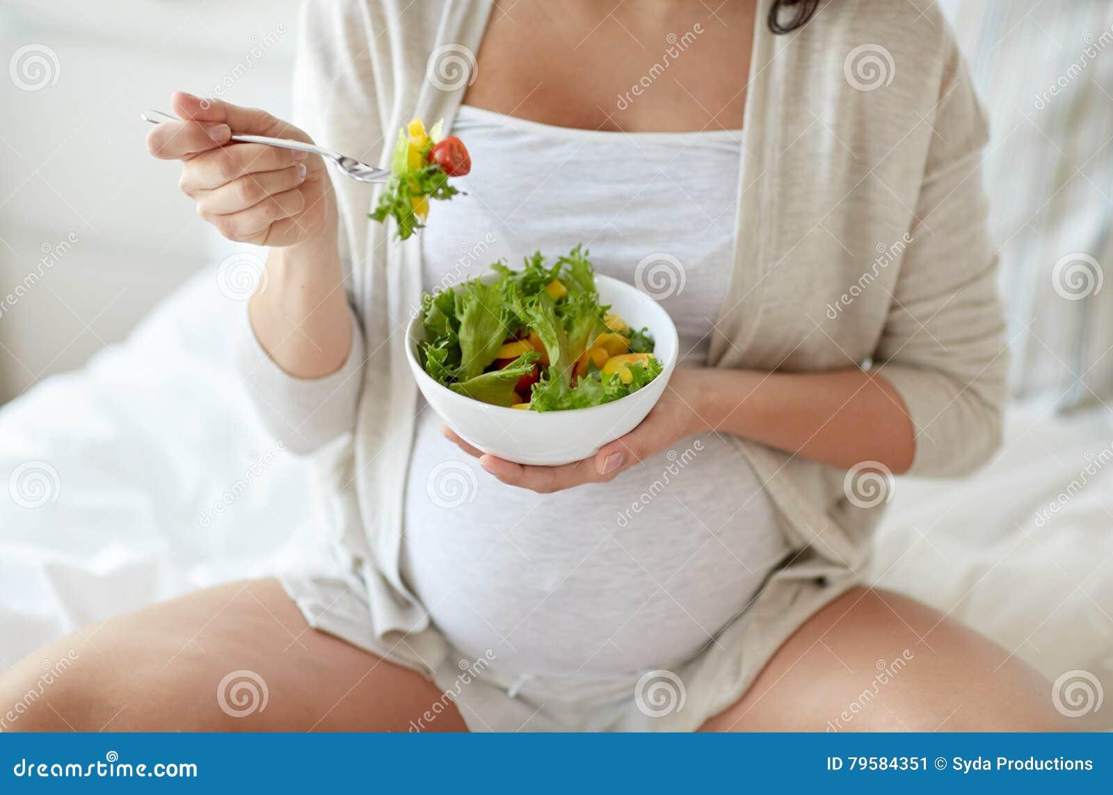 Sluit omhoog van zwangere vrouw die salade thuis eten