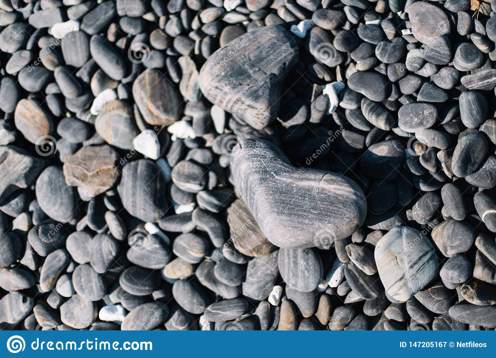 Sluit omhoog van zwarte rond gemaakte strandstenen en kiezelsteenstenen