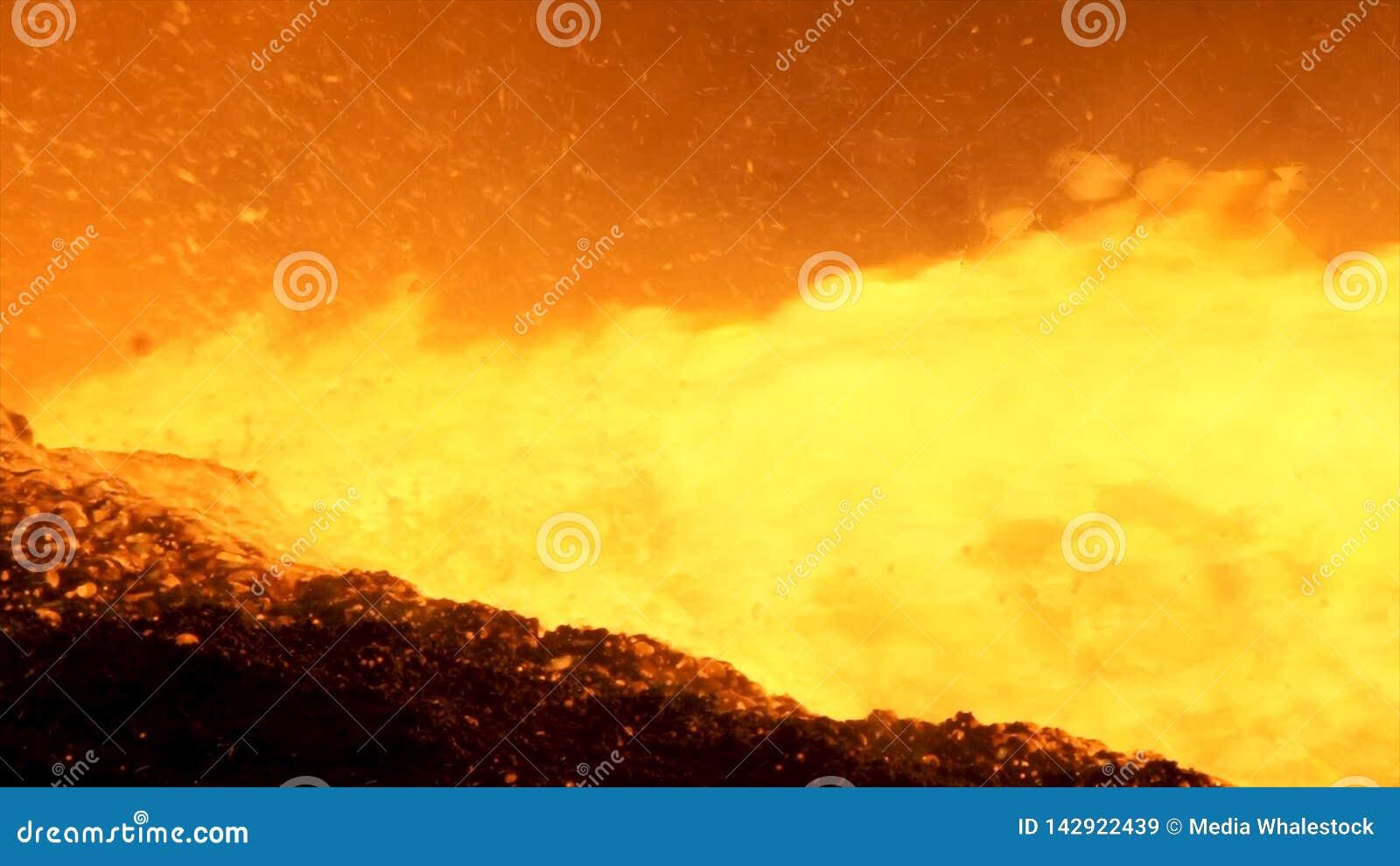 Sluit omhoog voor vloeibaar metaal die van hoogoven bij de metallurgische installatie stromen, zware industrieconcept Gesmolten g