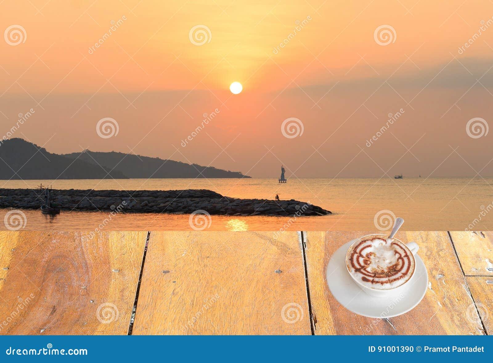 Sluit omhoog witte koffiekop op houten lijst en mening van zonsondergang of zonsopgangachtergrond