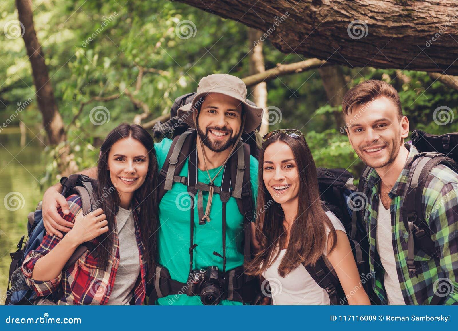 Sluit opgedoken portret van vier vrolijke vrienden in het de zomer aardige hout Zij zijn wandelaars, het lopen en het plukken pla