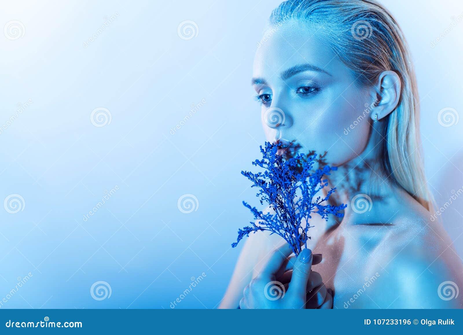 Sluit portret van jong mooi blond model met naakt maken omhoog, slicked omhoog achterhaar houdend een tak van blauwe bloemen