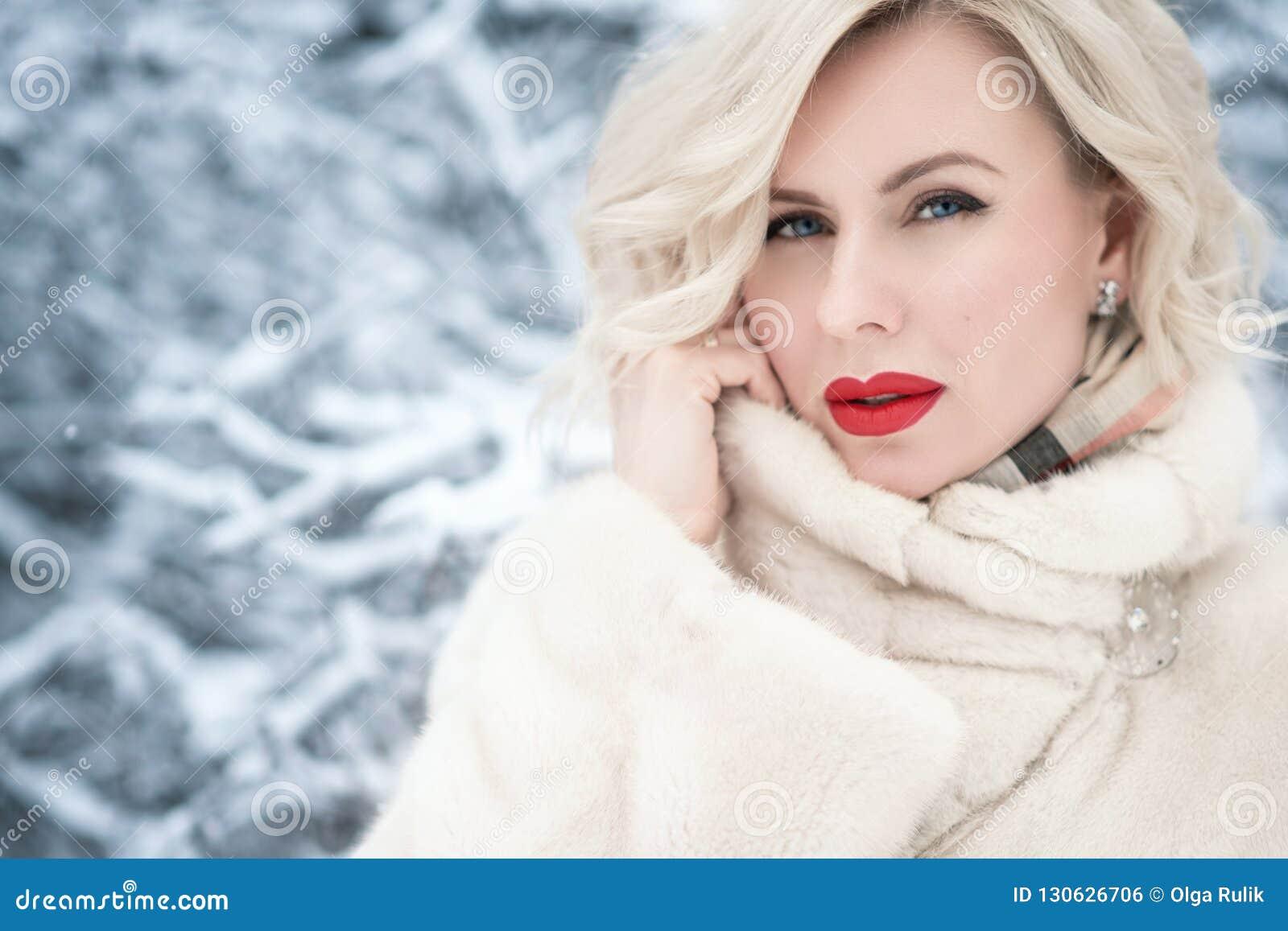 Sluit portret van mooie blonde blauw-eyed dame met perfect maken omhoog omhoog het houden van een kraag van haar luxueuze bontjas
