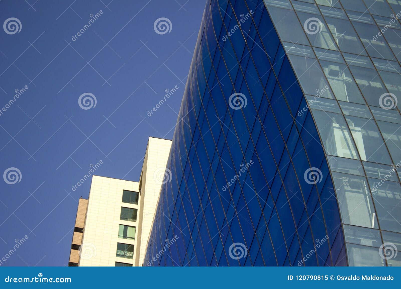 Sluit schot van een gebogen blauwe muur van het glasvenster van een modern en elegant corporatief gebouw