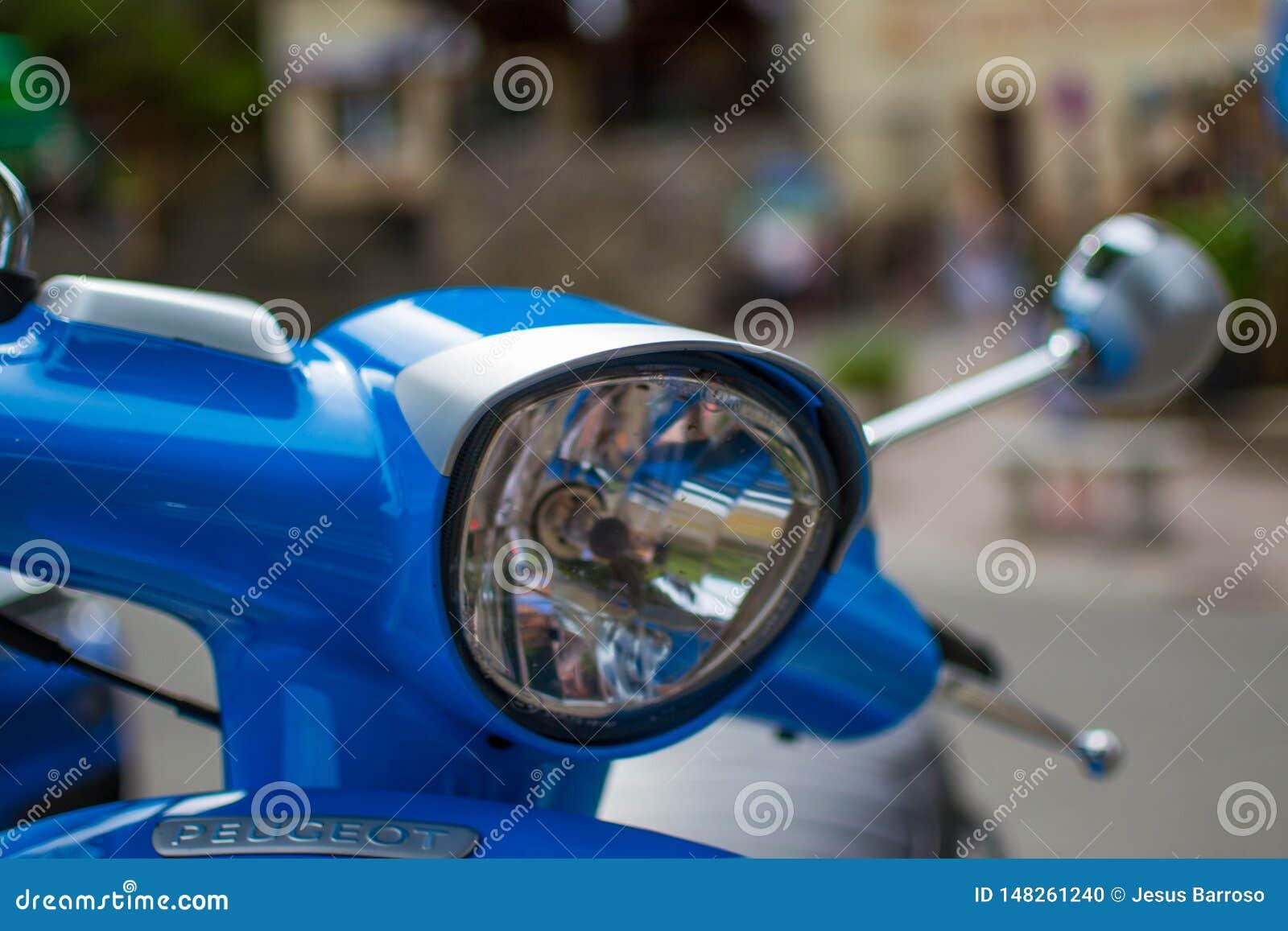 Sluit van de koplamp van een blauwe klassieke autoped met defocused omhoog achtergrond