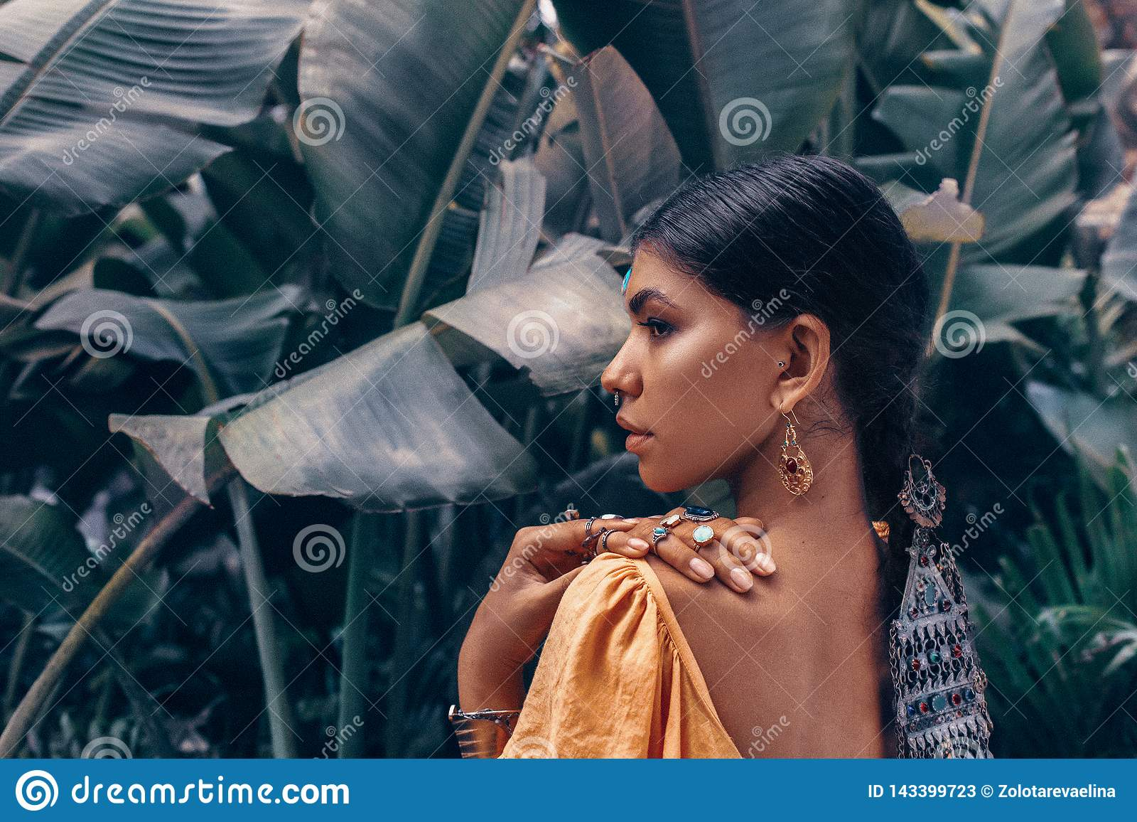 Sluit van mooie jonge modieuze vrouw met maken omhoog omhooggaande en modieuze bohotoebehoren stellend op natuurlijke tropische a