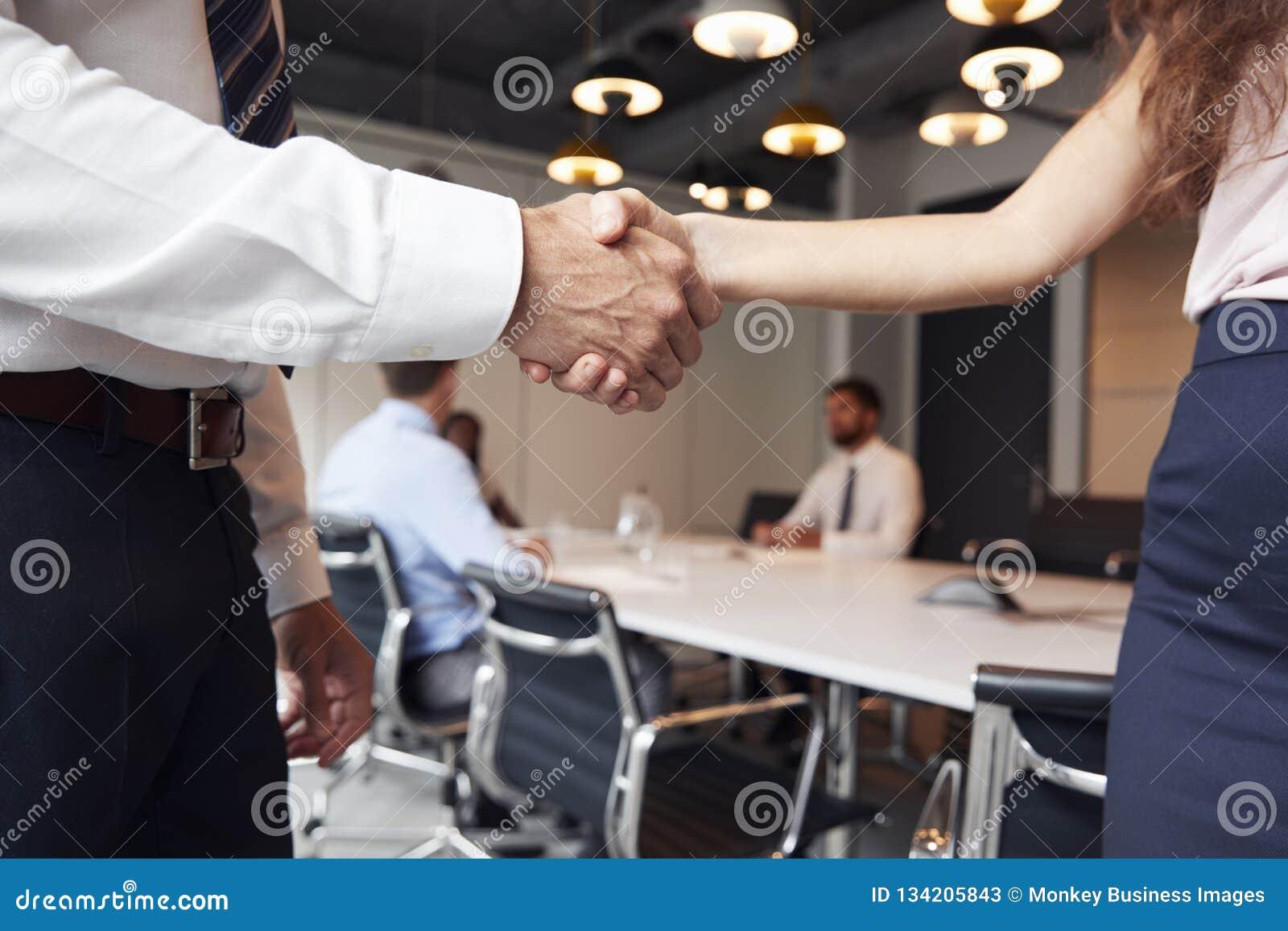 Sluit van Zakenman And Businesswoman Shaking indient omhoog Moderne Bestuurskamer met Collega s die rond Lijst op Achtergrond sam