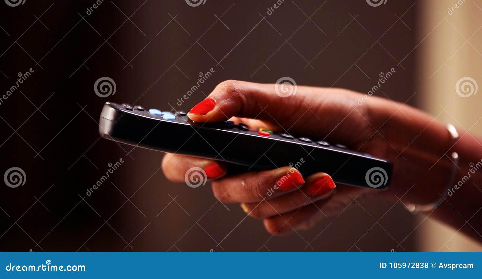 Slut upp av ändrande kanaler för TVfjärrkontroll och volymförhöjning, hållande ögonen på TV för tonårs- flicka i vardagsrummet el