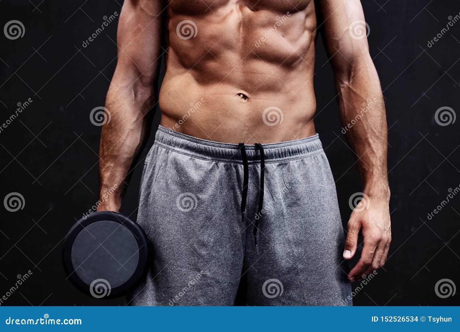 Slut upp av den muskul?sa kroppsbyggaregrabben som g?r ?vningar med vikter ?ver svart bakgrund