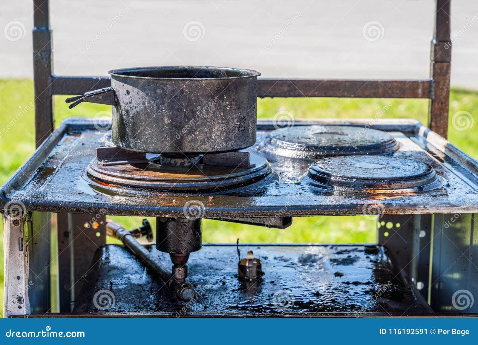 Slut upp av en bränd svart gasugn som överst täckas med fett, en bränd kruka