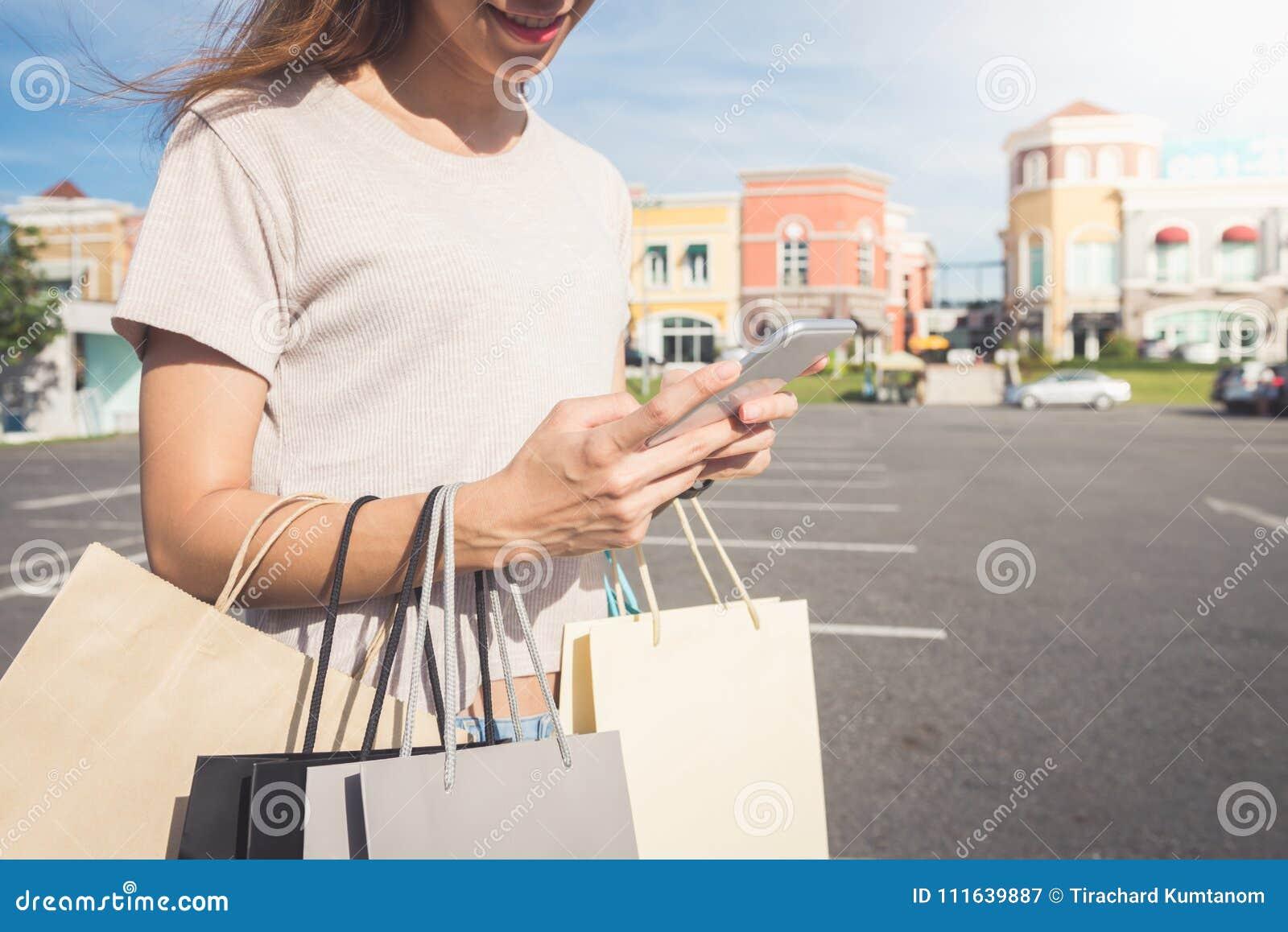 Slut upp av en håll för ung kvinna påsar för en shopping i henne hand och prata på hennes telefon, når att ha shoppat