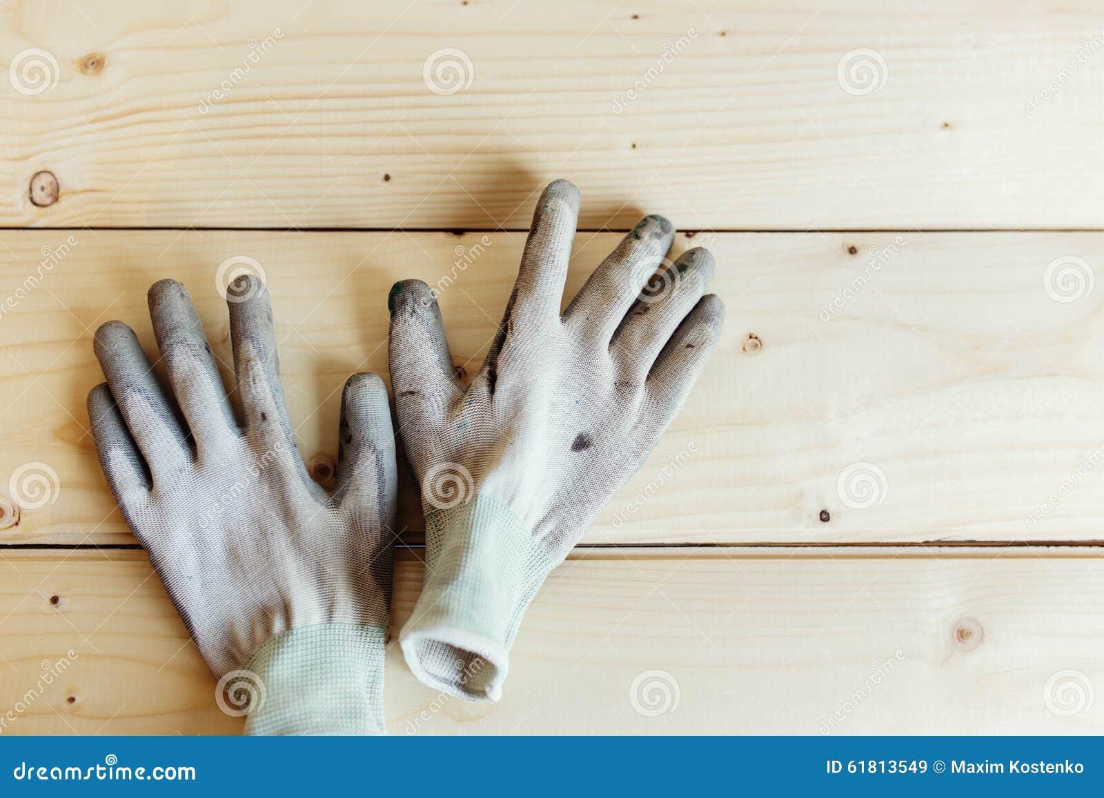 Slut upp av funktionsdugliga handskar mot trä
