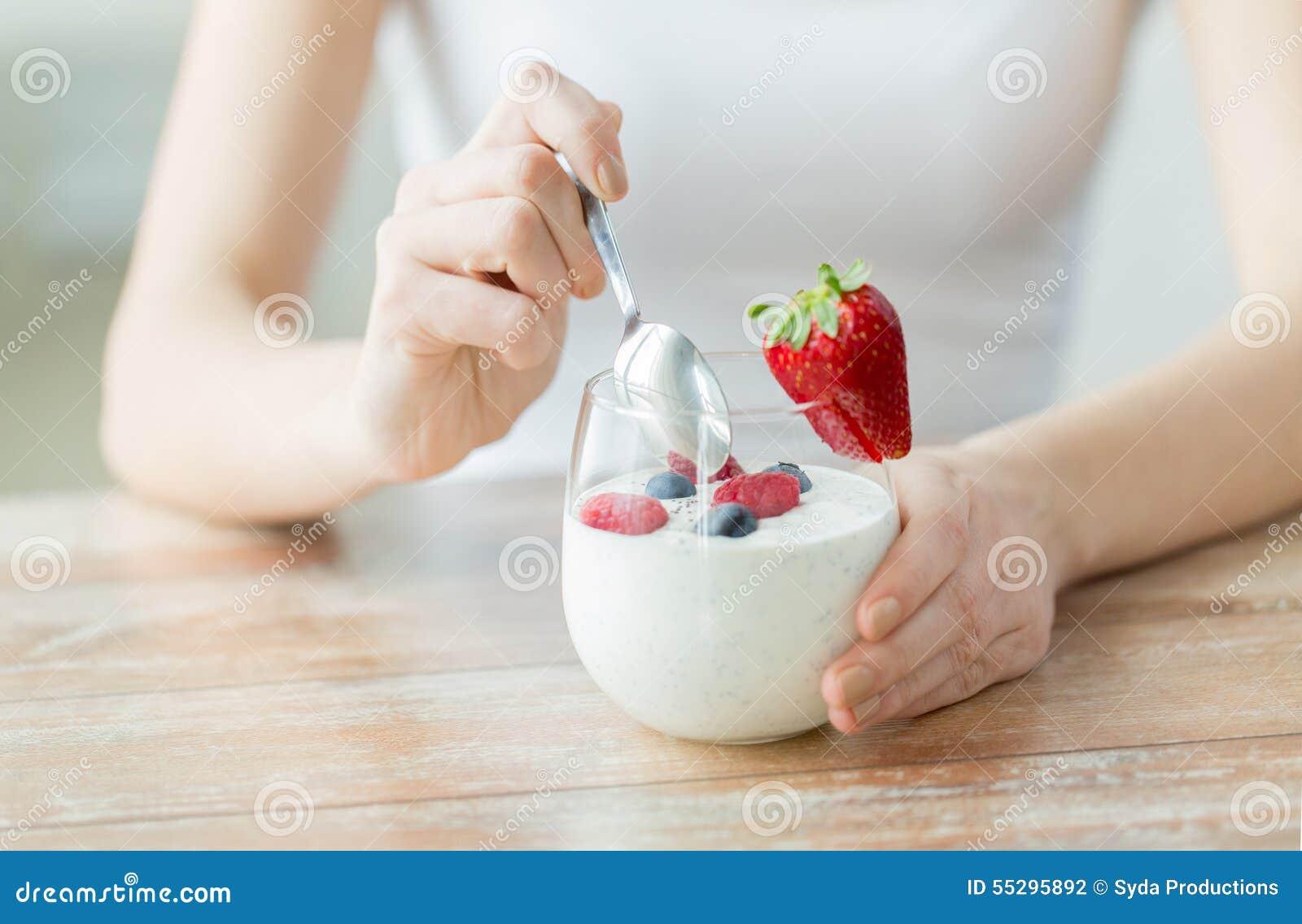 Slut upp av kvinnahänder med yoghurt och bär