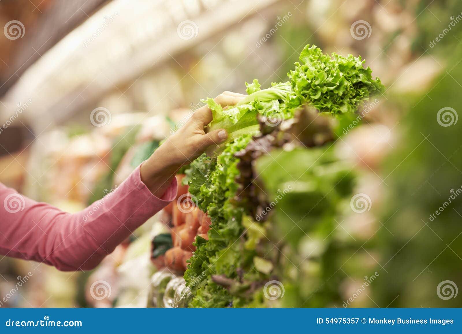 Slut upp av kvinnan som väljer sallad i supermarket