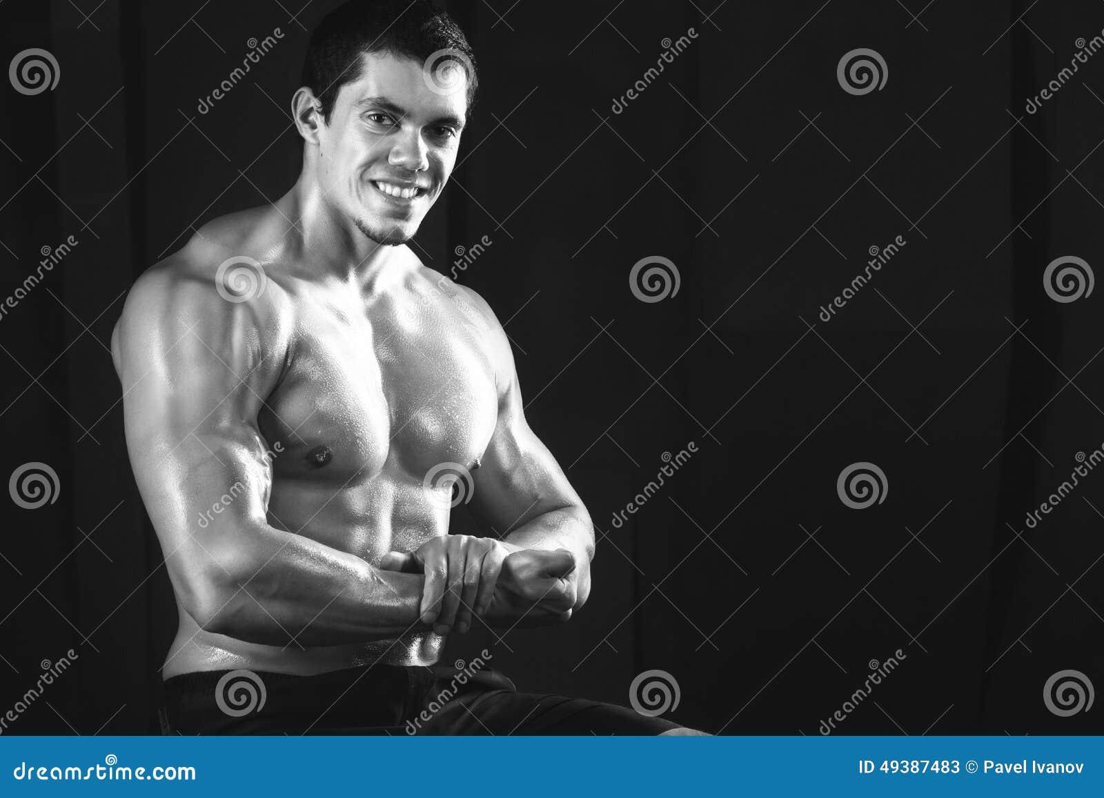 Slut upp av lyftande vikter för ung muskulös man över mörker