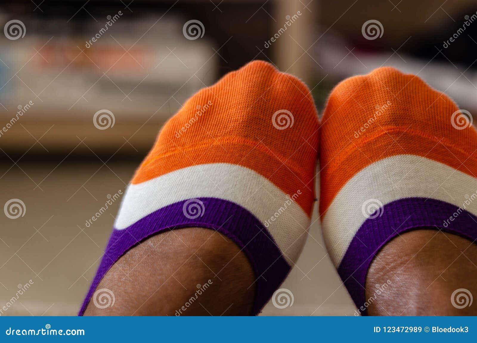 Slut upp av mång--färgade sockor på en svart kvinna