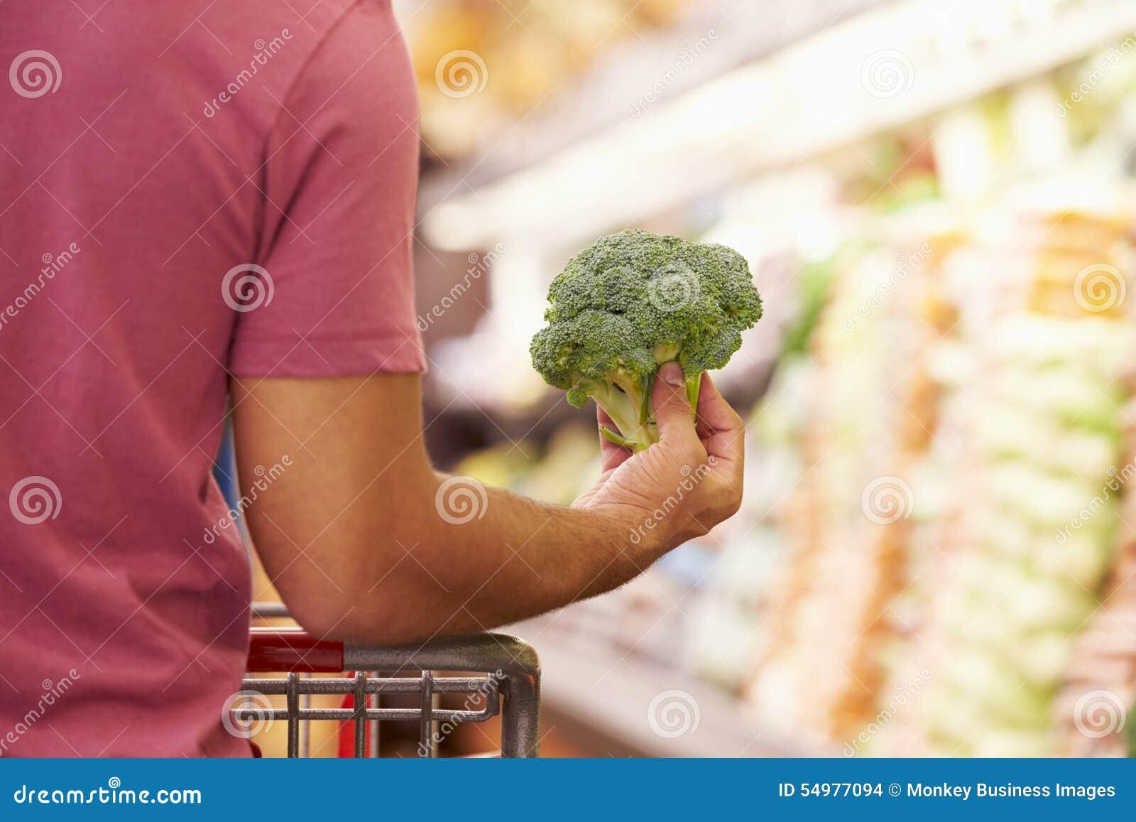 Slut upp av mannen som väljer broccoli i supermarket