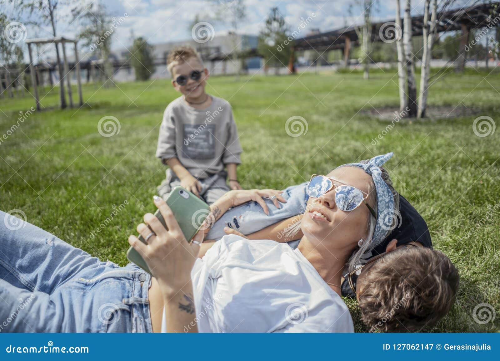 Slut upp av mumen och söner som ligger i parkera på grönt gräs lycklig begreppsfamilj
