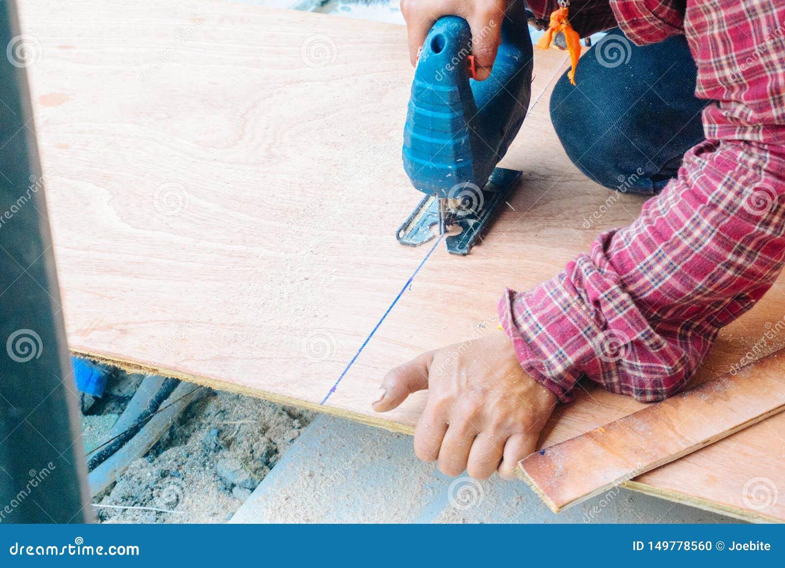 Slut upp den asiatiska mansnickaren som använder elektriska sågar för att klippa det stora brädet av trä i en konstruktionsplats
